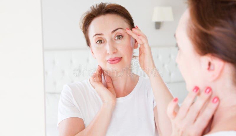 Mulher da Idade M?dia que olha no espelho na cara do enrugamento na testa Menopausa, enrugamentos e conceito antienvelhecimento d imagem de stock royalty free
