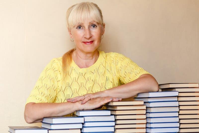 Mulher da idade da reforma e lotes dos livros imagem de stock