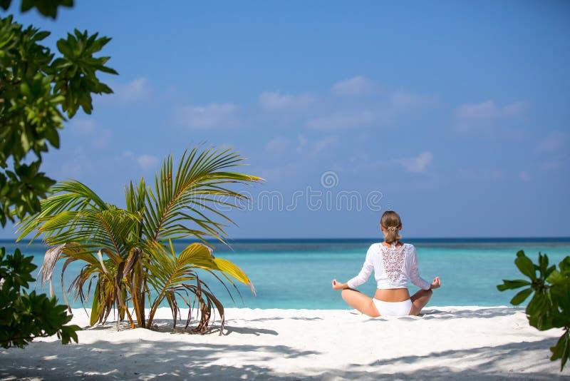 Mulher da ioga da meditação que medita na praia tropical sereno Menina que relaxa na pose dos lótus no momento calmo do zen na ág imagens de stock
