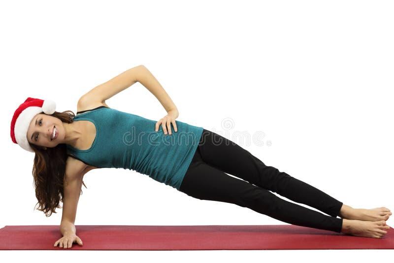 Mulher da ioga do Natal na pose lateral da prancha imagens de stock royalty free