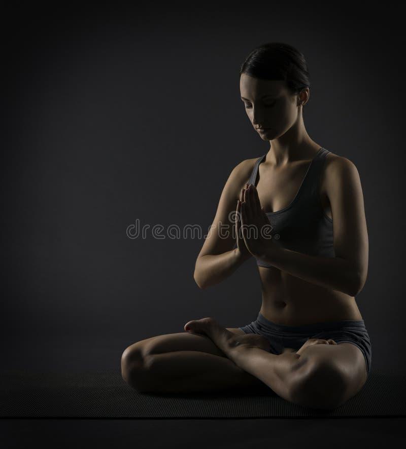 A mulher da ioga medita o assento na pose dos lótus Silhoue imagens de stock royalty free
