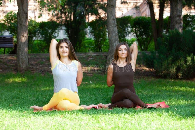 Mulher da ioga na ioga da grama verde exterior A mulher feliz que faz exercícios da ioga, medita no parque imagem de stock