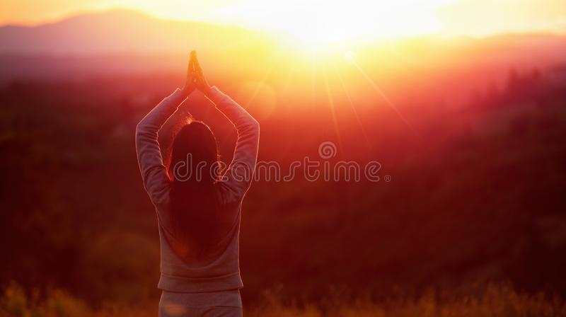 Mulher da ioga que medita no por do sol fotos de stock
