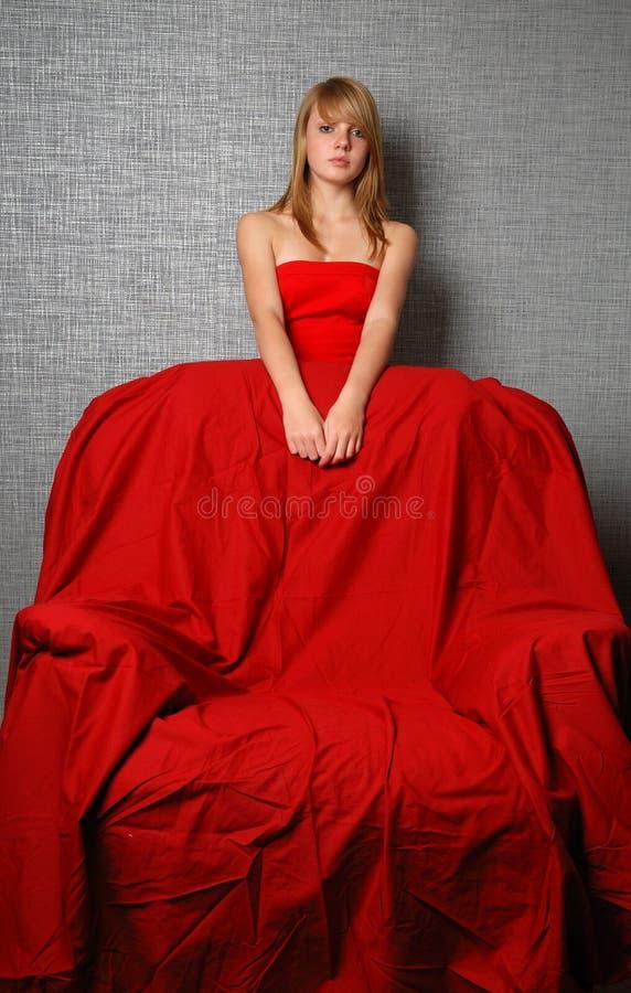 Mulher da juventude na poltrona vermelha e grande foto de stock