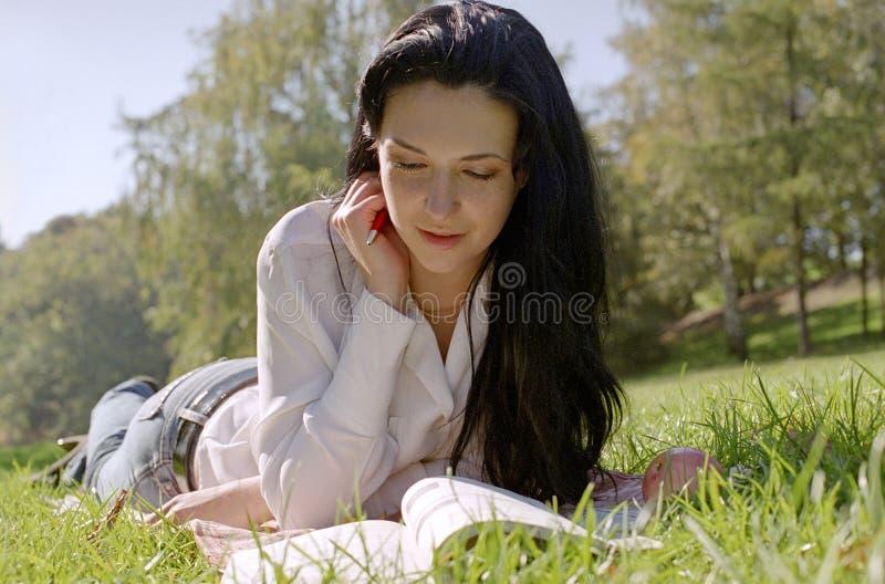 Mulher da leitura em uma grama imagens de stock royalty free