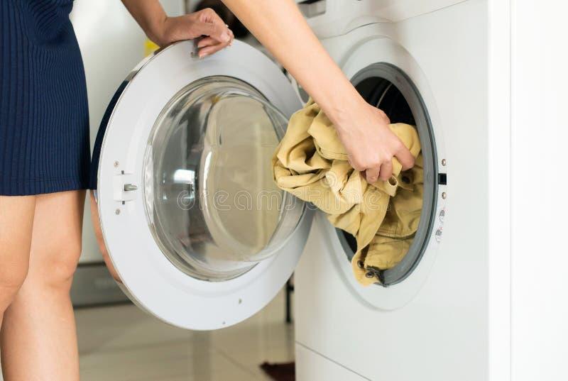 Mulher da mão que obtém na roupa suja na máquina de lavar que faz a lavanderia em casa fotos de stock