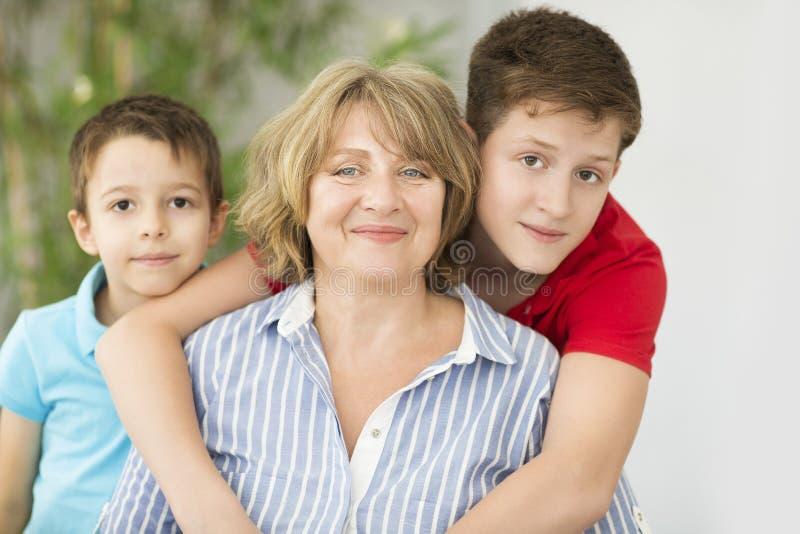 mulher da Meados de-idade com os dois meninos internos imagem de stock