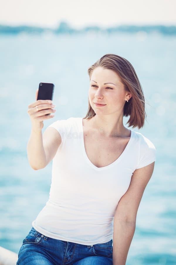 Mulher da menina que olha o telefone celular que faz o selfie foto de stock