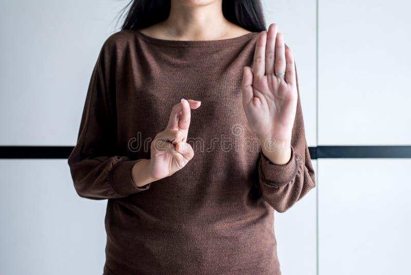 Mulher da mentira com os dedos de cruzamento da mão que dizem o mentiroso e que enganam-se, conceito do dia dos enganados, sinal fotos de stock