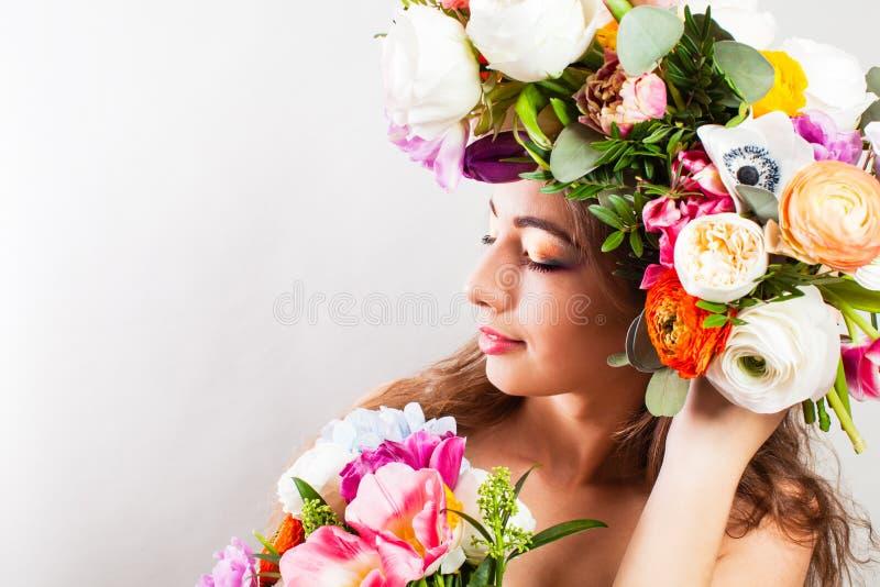 A mulher da mola com flores coloridas envolve-se e ramalhete fotografia de stock royalty free