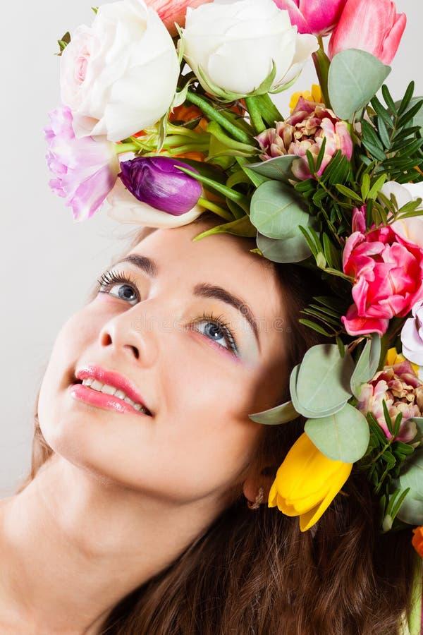A mulher da mola com flores penteado e arco-íris compõe imagens de stock