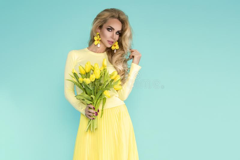 Mulher da mola Menina do modelo do verão da beleza com a roupa colorida, guardando um ramalhete de flores amarelas da mola fotografia de stock royalty free