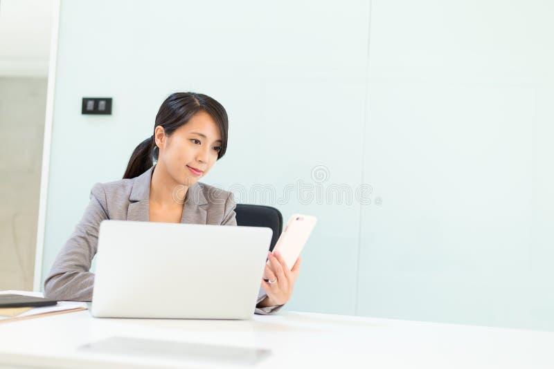 Mulher da mulher de negócios que usa o telefone celular e o laptop no confe imagem de stock royalty free