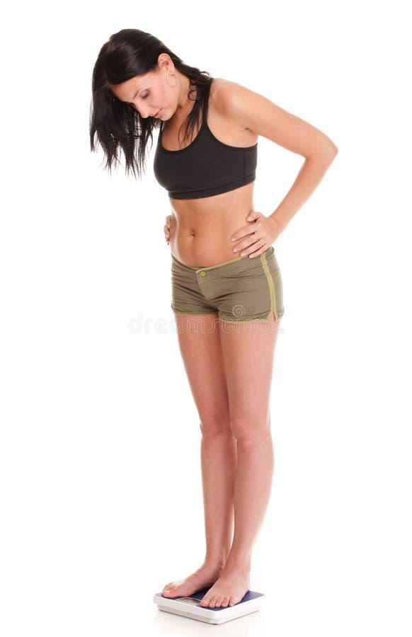 Mulher da perda de peso na escala feliz imagens de stock royalty free