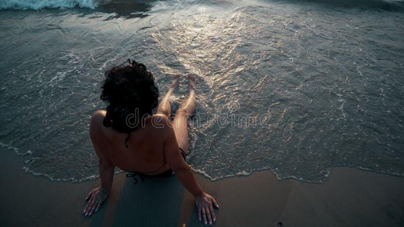 Mulher da praia do bronzeado que bronzea-se os pés que relaxam a natação na água do oceano com o desenho do sol do por do sol no  fotografia de stock