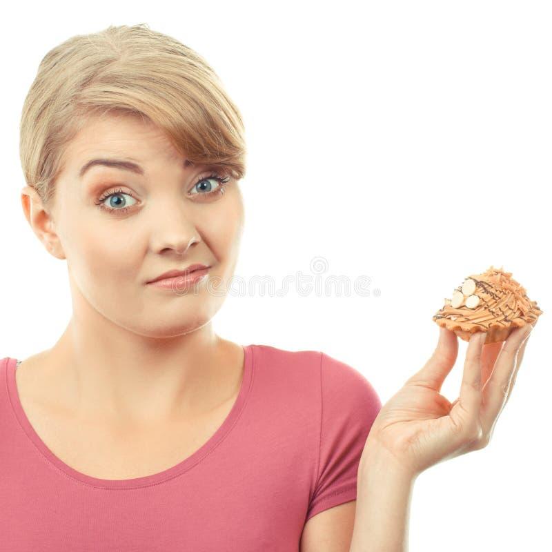 Mulher da preocupação que guarda o queque fresco, o conceito da dieta e a nutrição saudável imagem de stock