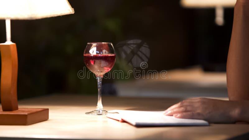 Mulher da raça misturada que lê livro emocionante e que bebe o vinho tinto no café, close up fotografia de stock