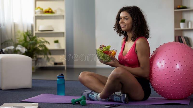 Mulher da raça misturada que senta-se no assoalho no sportswear e que come a salada, cuidado do corpo imagem de stock