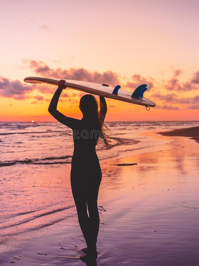 A mulher da ressaca vai a surfar Menina com prancha em uma praia no por do sol ou no nascer do sol imagem de stock
