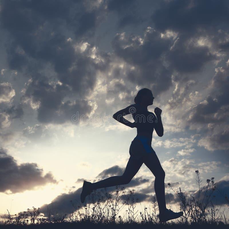 A mulher da silhueta corre sob o céu azul com nuvens foto de stock royalty free