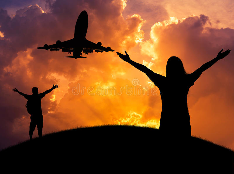 A mulher da silhueta e a posição do homem levantada acima dos braços comemoram durante o voo do avião no por do sol imagens de stock royalty free