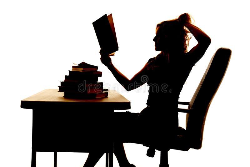 Mulher da silhueta no cabelo da tração do livro da mesa fotos de stock