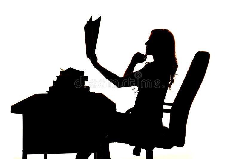 Mulher da silhueta no livro da mesa que pensa acima imagens de stock royalty free