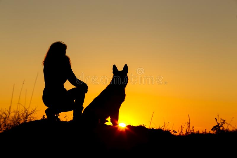 Mulher da silhueta que anda com um cão no campo no por do sol, animal de estimação que senta-se perto do pé da menina na natureza fotografia de stock royalty free