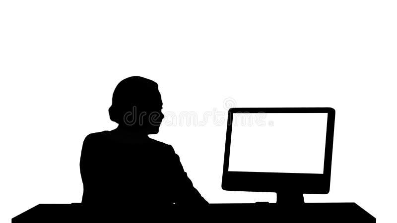 Mulher da silhueta que trabalha olhando o monitor no escritório imagens de stock royalty free