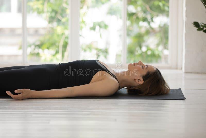 A mulher da vista lateral que encontra-se na esteira faz a pose do cadáver dentro imagem de stock royalty free