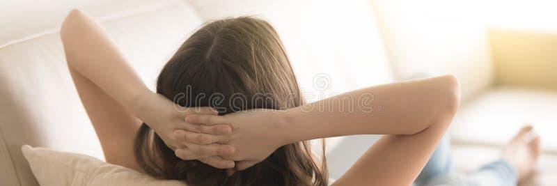 Mulher da vista panorâmica que encontra-se no sofá que guarda as mãos atrás da cabeça fotos de stock royalty free