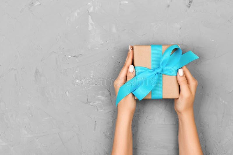 A mulher da vista superior entrega guardar a caixa atual com curva azul no fundo cinzento com espaço da cópia fotografia de stock