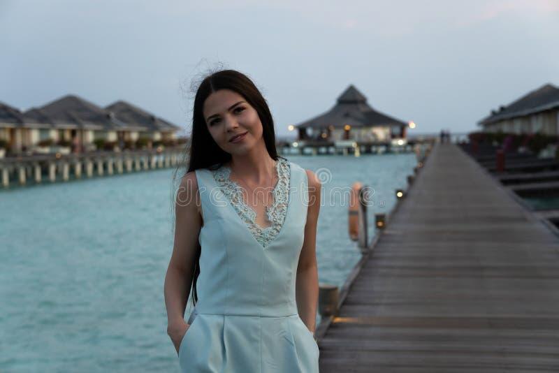 Mulher das férias da praia que anda na ponte sobre o hotel de luxo dos bungalows no fundo fotos de stock
