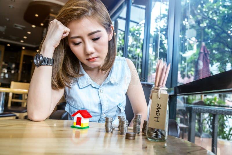 Mulher de Ásia com modelo da casa e garrafa do dinheiro fotos de stock royalty free