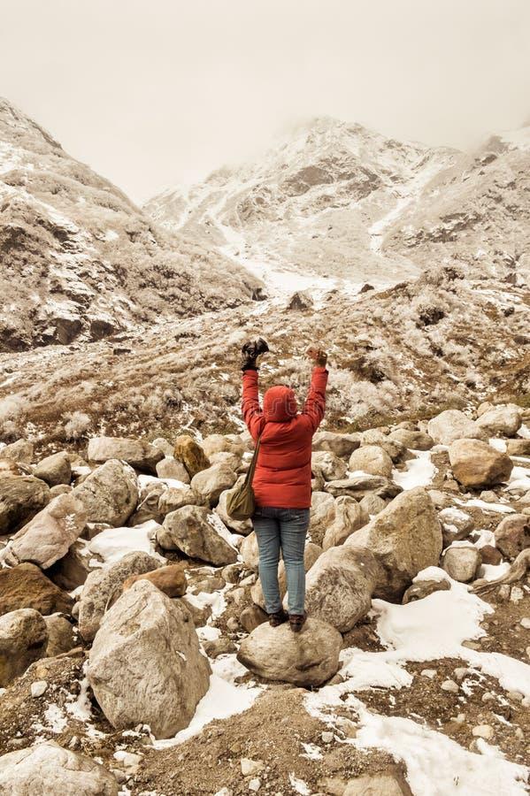 A mulher de Ásia do caminhante no vestido vermelho gerencie para trás estar e esticar seus braços aumentados no céu após a caminh fotos de stock royalty free