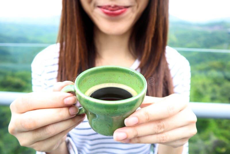 Mulher de Ásia que aprecia a manhã sereno bonita que olha o céu do cenário da paisagem da natureza das montanhas que começa o caf foto de stock