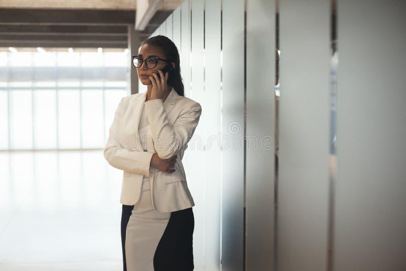 Mulher de óculos do negócio moreno novo que fala pelo telefone celular foto de stock