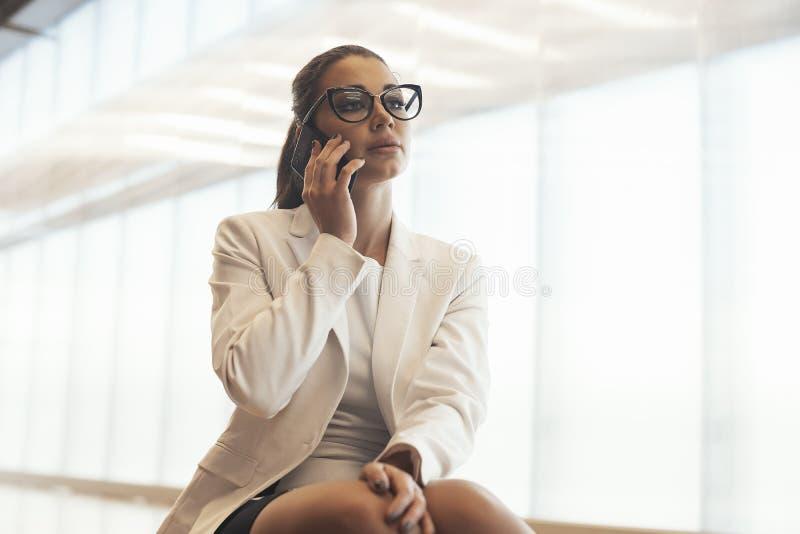 Mulher de óculos do negócio novo no revestimento branco que fala pelo telefone celular imagens de stock