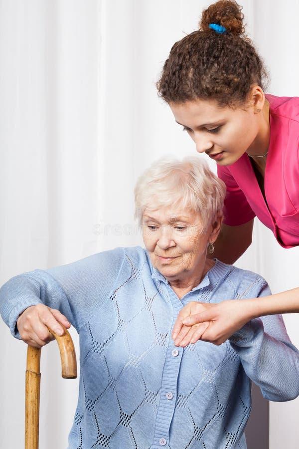 A mulher de ajuda da enfermeira levanta-se fotos de stock royalty free
