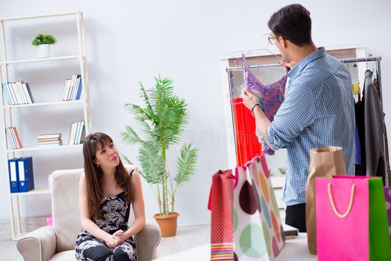 A mulher de ajuda do assistente de loja com escolha de compra imagem de stock