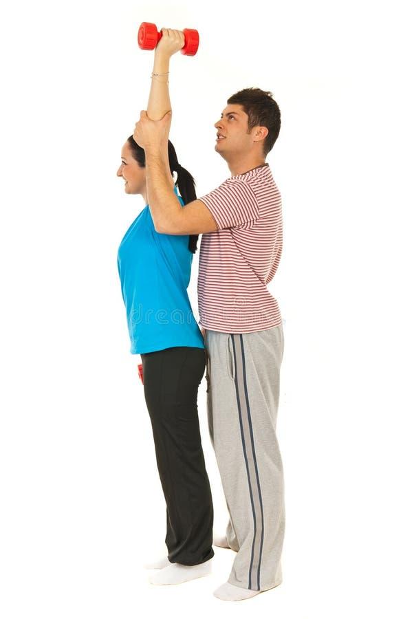 Mulher de ajuda do instrutor a fazer exercícios fotografia de stock