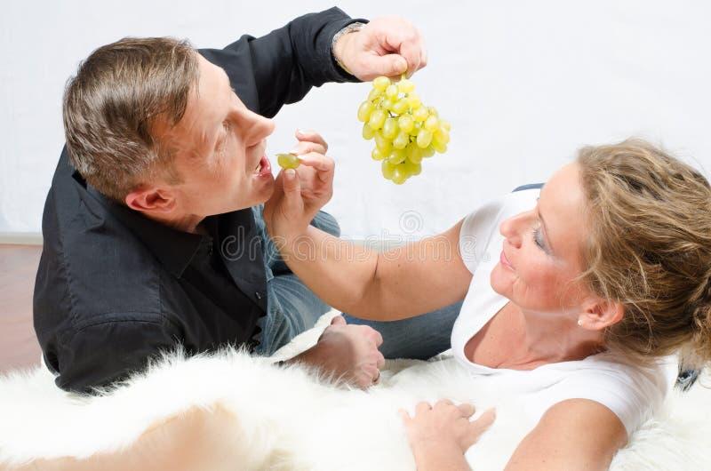 Mulher de arrelia do homem com uvas foto de stock