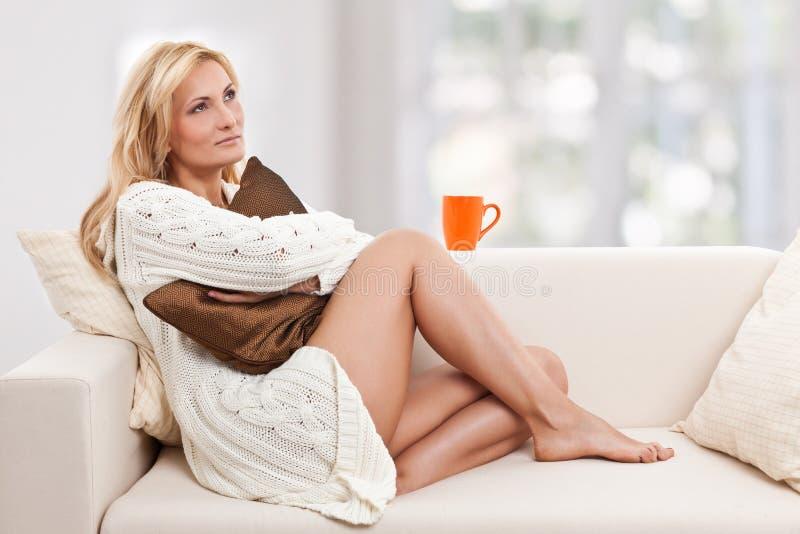 Mulher de Blondie em um sofá com um copo orange-colored imagem de stock