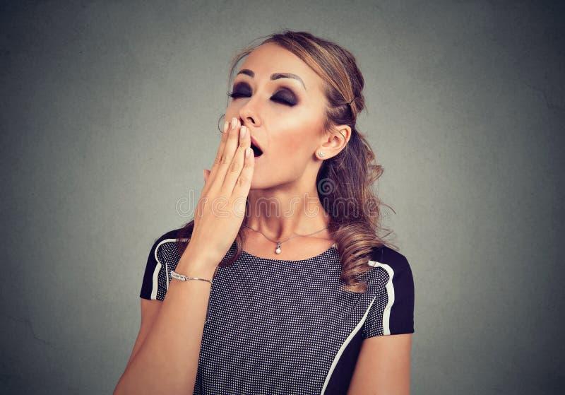 Mulher de bocejo cansado que cobre sua boca aberta larga com a mão foto de stock royalty free