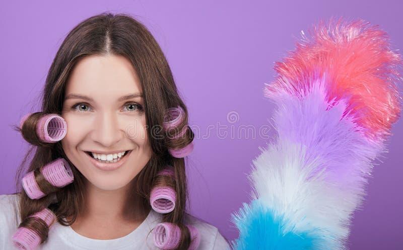 Mulher de cabelo castanho sorridente, de olhos verdes, em curlers imagem de stock