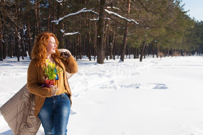 Mulher de cabelo encaracolado agradável que olha na distância com seu revestimento sobre o ombro e floresta do inverno no fundo fotografia de stock royalty free