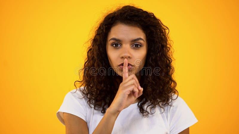 Mulher de cabelo encaracolado que mostra o gesto do silêncio, mantendo segredos, informação privada fotos de stock royalty free