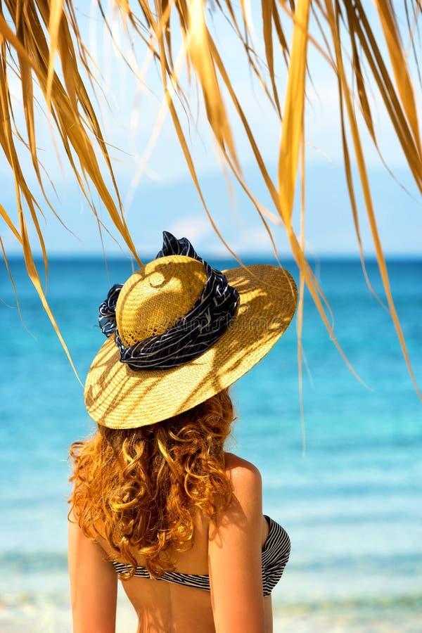 Mulher de cabelo encaracolado que olha o mar imagem de stock