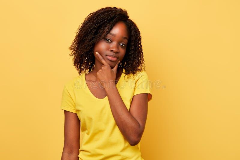 Mulher de cabelo escura pensativa com os dedos em seu queixo que olha a câmera imagem de stock royalty free