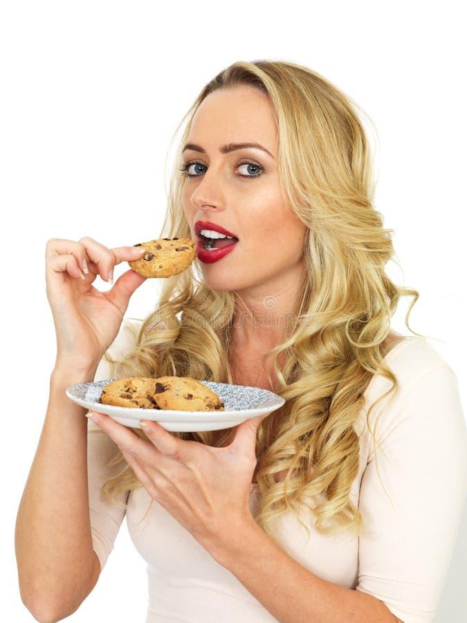 Mulher de cabelo loura atrativa nova que come biscoitos imagens de stock